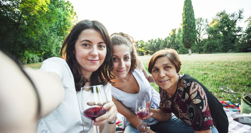 two young women and their mother having wine outside