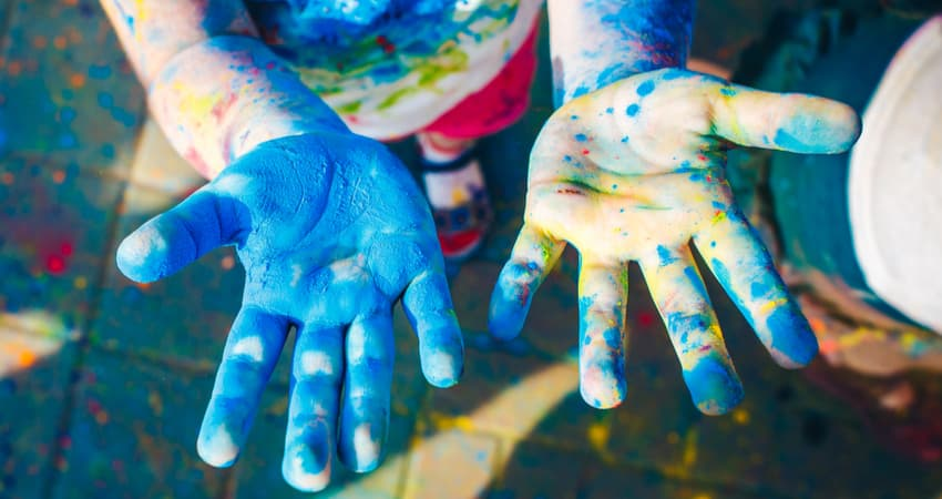 a child's hands covered in paint at a festival