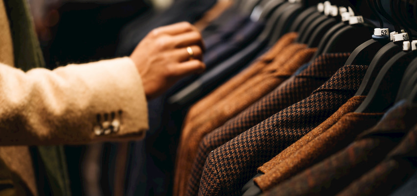 a mall visitor inspects a rack of suit jackets at the Mall at Millennia in Orlando Florida