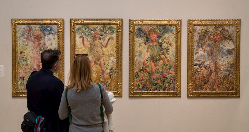 visitors admire a lineup of paintings at The Mennello Museum of American Art near Orlando Florida