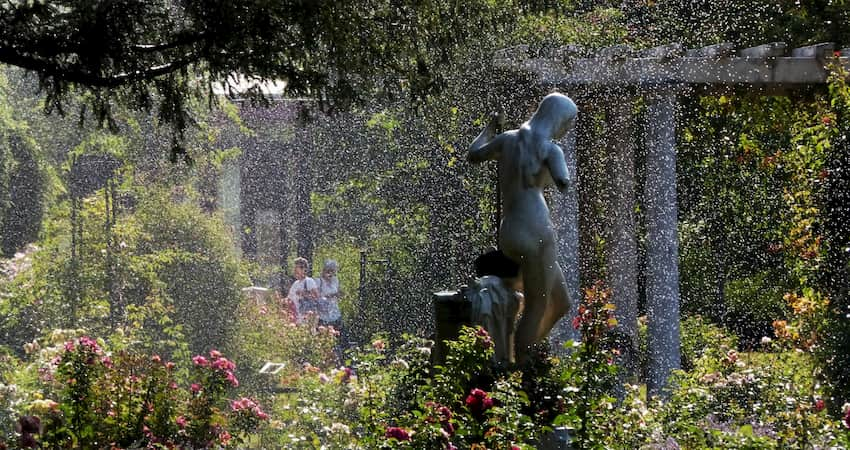 a misty rain settles over metal statues and surrounding gardens at Albin Polasek Museum & Sculpture Gardens near Orlando Florida