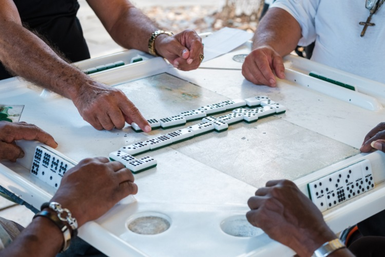 Elderly people's hands playing dominos in Domino Park