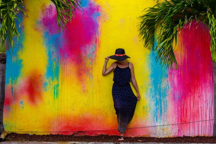 Woman in floppy hat and navy blue maxi dress standing against wall painted bright blue, pink and yellow