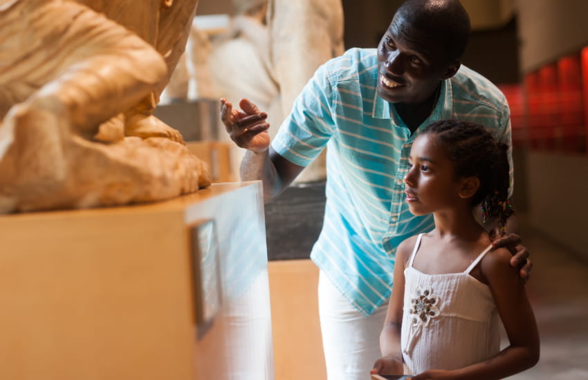a chaperone and student admire a stone sculpture in an art museum