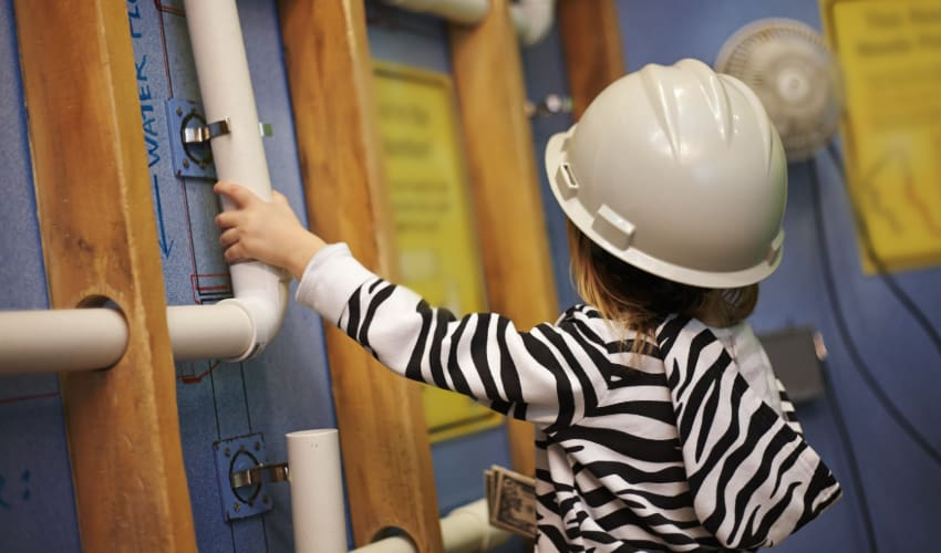a small child wears a construction helmet and holds a pipe in a science museum
