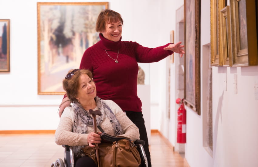 two women, one standing and one in a wheelchair, tour an art exhibit in a museum