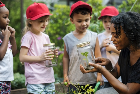 Children holding specimens in jars outdoors