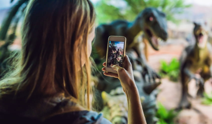 a woman used her smart phone to take a picture of dinosaur models in a science museum