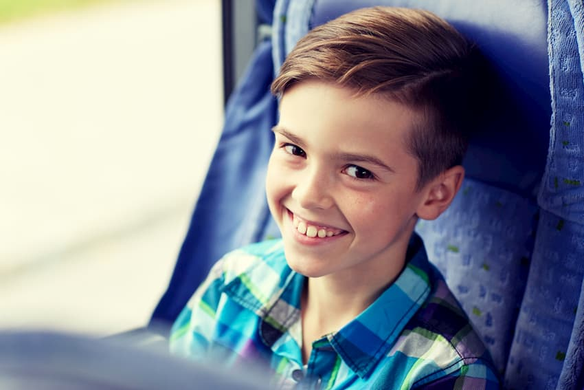 child smiling seated on a charter bus