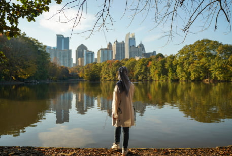 a woman in a headscarf admires the Atlanta skyline from Piedmont Park