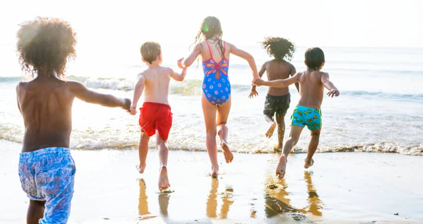 A group of kids running at the beach