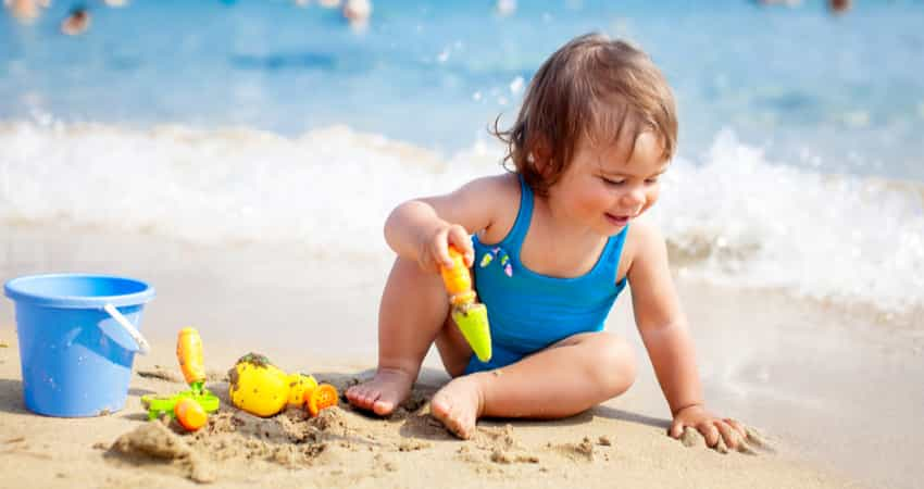 A young child playing with sand at the beach