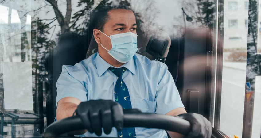 A charter bus driver wearing a mask while behind the wheel.