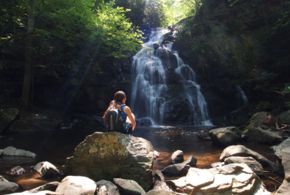 A hiker sits on a rock near a waterfall in the Great Smoky Mountains
