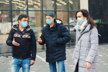 A group of people wearing masks talking on the sidewalk