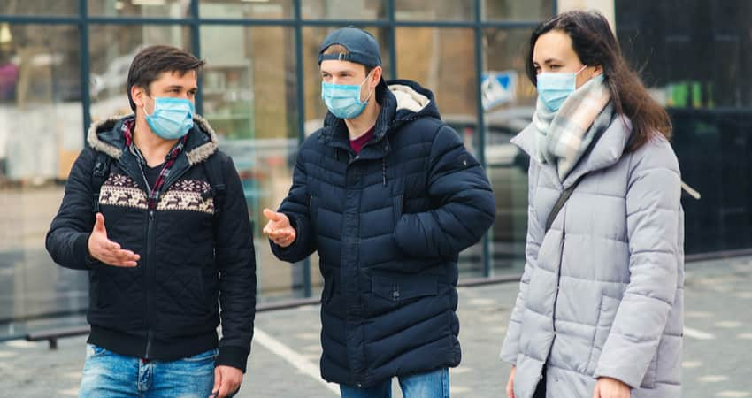 A group of three people wearing masks and winter clothes while talking on a sidewalk.
