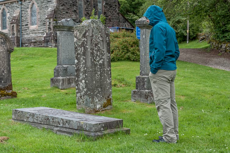 Man in blue jacket standing by grave