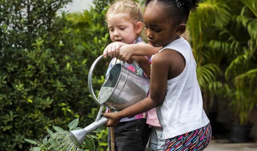 Two children watering a garden