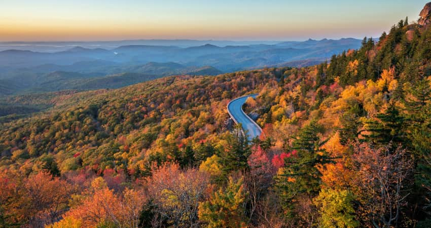 The Blue Ridge Parkway winds through autumn-colored trees and mountainsides