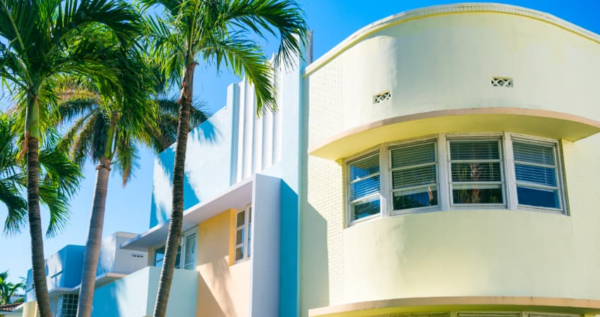 Art deco-style buildings in Miami, next to a palm tree