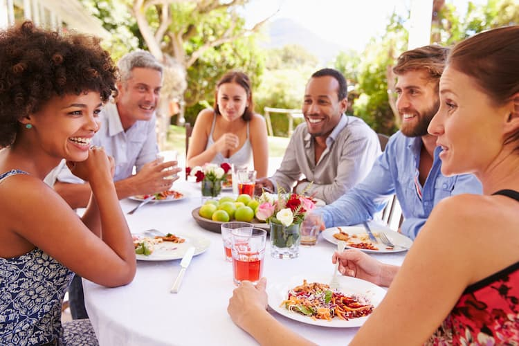 Large group laughing over food outside