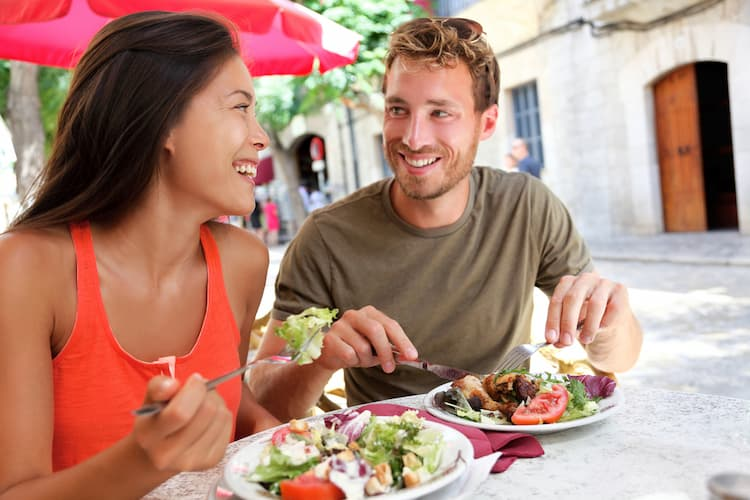 Young couple eating salad together