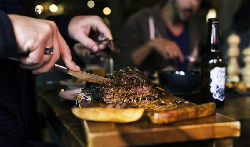 Close up of a man cutting a steak