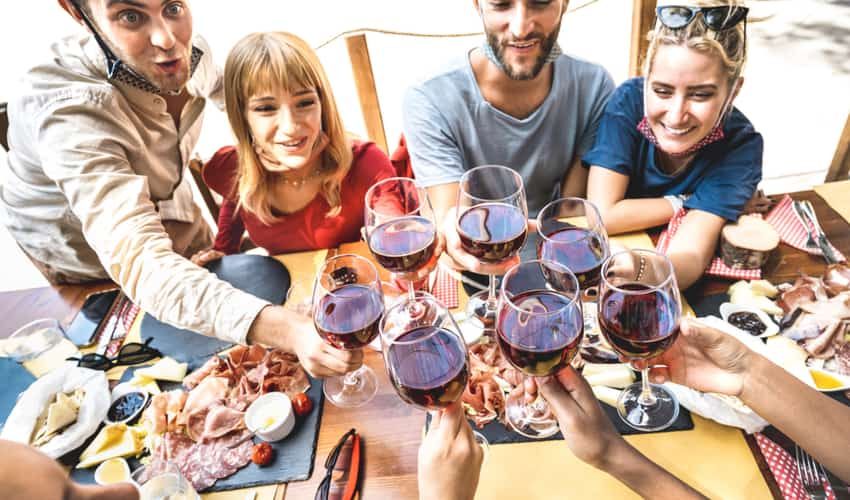 A group of friends toasting glasses of wine over dinner