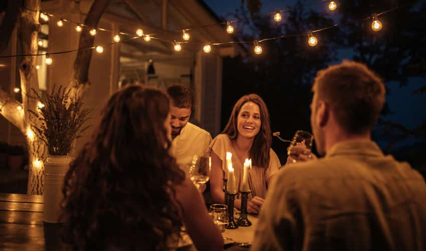 People having dinner on a patio under lights in the evening