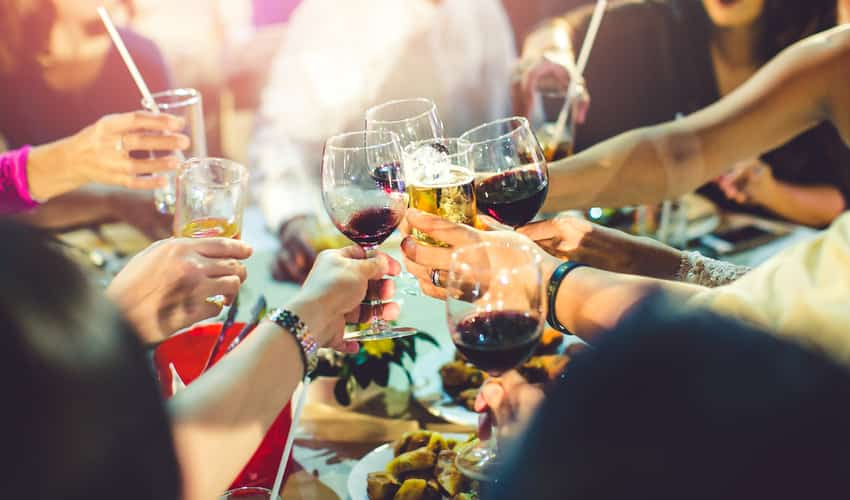 Friends toasting wine over food