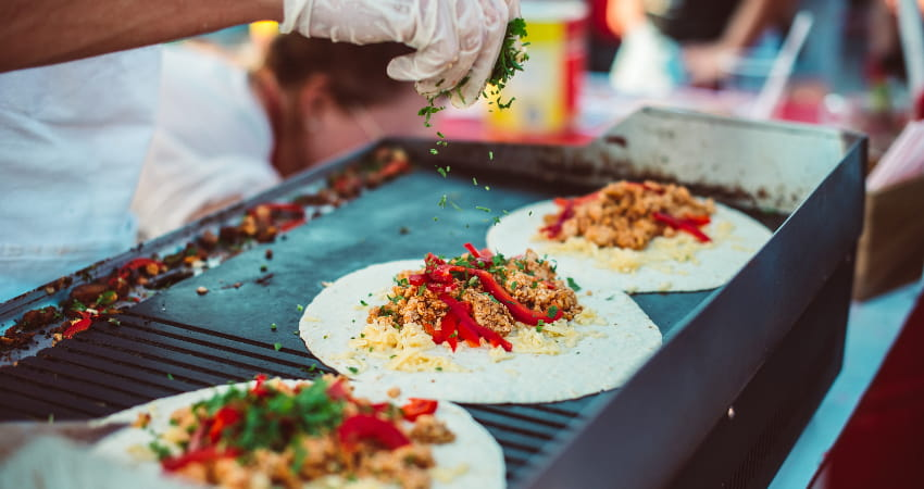 A chef heats up tortillas filled with toppings on a flat-top grill