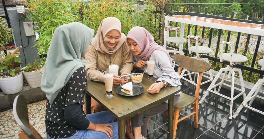 Three women laugh and eat a snack on an outdoor patio surrounded by plants