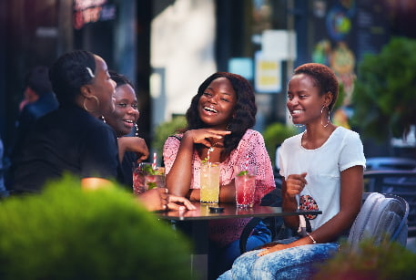A group of friends enjoy colorful cocktails on a restaurant patio