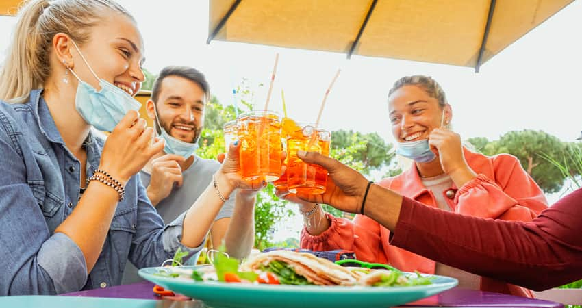 A group of friends toasting drinks over lunch under a patio umbrella