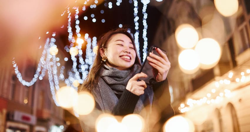 A woman smiles at her phone while surrounded by bright holiday lights