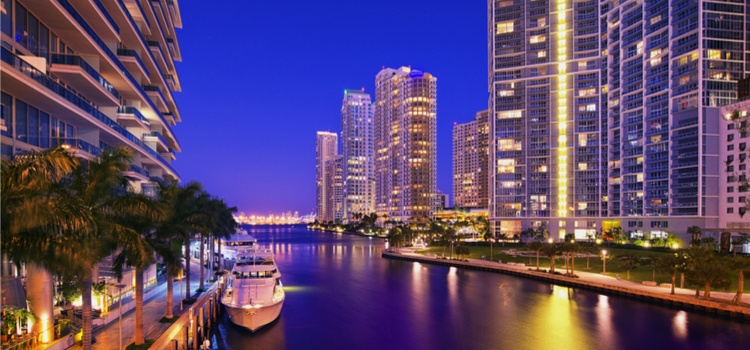 nighttime miami skyline with boat and water
