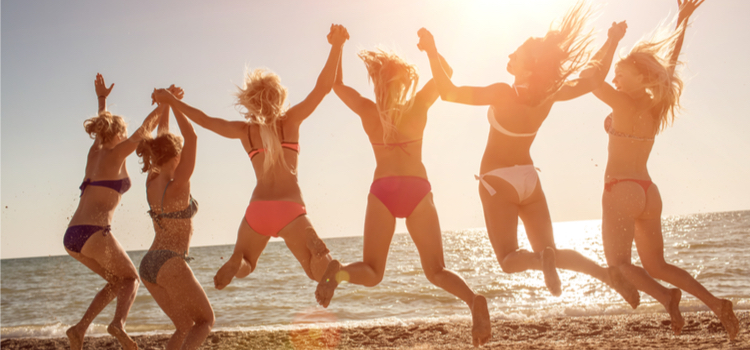 group of six girls jumping on the beach